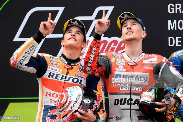 Ducati Team's Spanish rider Jorge Lorenzo first placed and Repsol Honda Team's Spanish rider Marc Marquez second placed look up in memory of late...