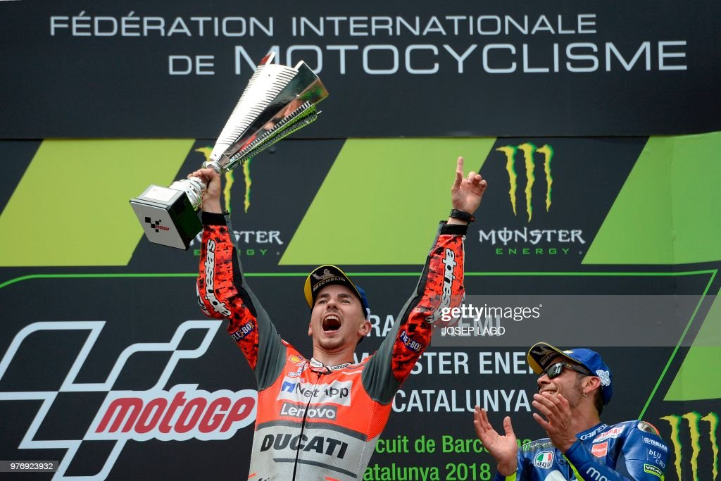 TOPSHOT - Ducati Team's Spanish rider Jorge Lorenzo (L), first placed, celebrates next to Movistar Yamaha MotoGP's Italian rider Valentino Rossi (R), third place, on the podium of the Catalunya MotoGP Grand Prix race at the Catalunya racetrack in Montmelo, near Barcelona on June 17, 2018.