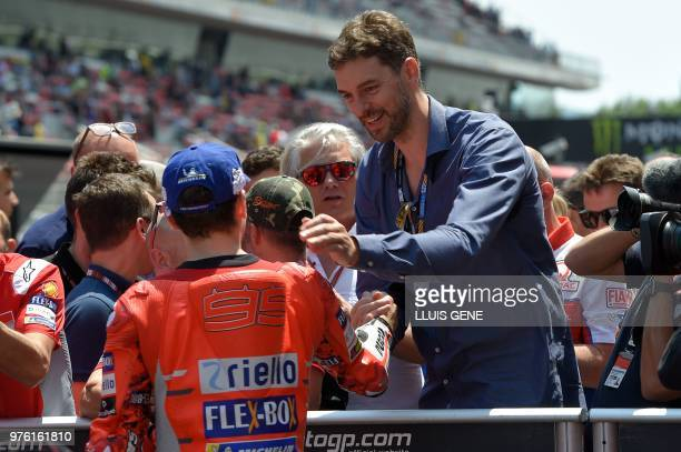 Ducati Team's Spanish rider Jorge Lorenzo is congratulated by Spanish basketball player Pau Gasol after taking the pole position during the Catalunya...