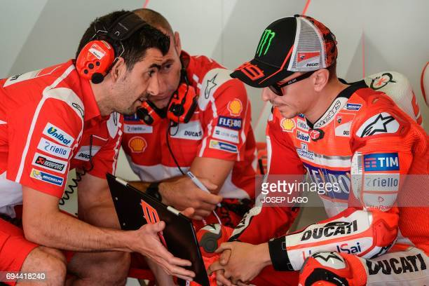 Ducati Team's Spanish rider Jorge Lorenzo listen to engineers during the third MotoGP free practice session of the Moto Grand Prix de Catalunya at...
