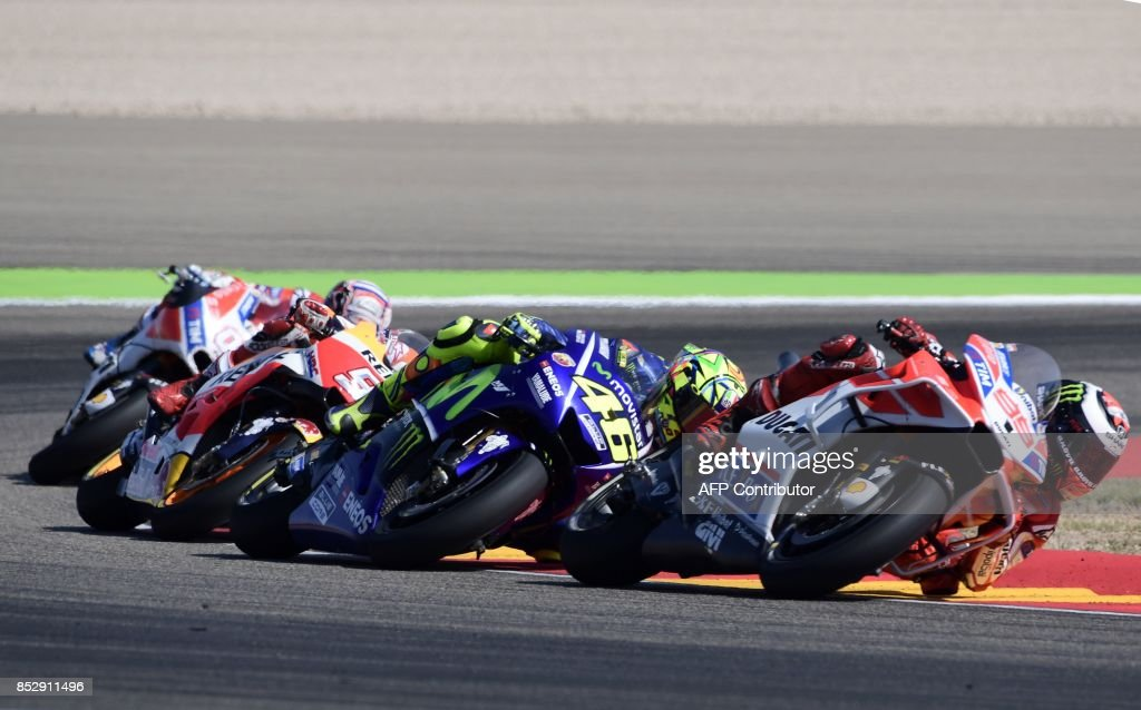 Ducati Team's Spanish rider Jorge Lorenzo (R), Movistar Yamaha MotoGP's Italian rider Valentino Rossi (2R) and Repsol Honda Team's Spanish rider Marc Marquez (2L) ride during MotoGP race of the Moto Grand Prix of Aragon at the Motorland circuit in Alcaniz on September 24, 2017. /