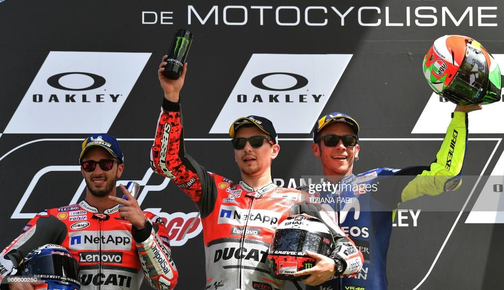 Ducati Team's Spanish rider Jorge Lorenzo (C) poses on the podium with second placed Ducati's Team rider Italian Andrea Dovizioso (L) and third placed Movistar Yamaha's Italian rider Valentino Rossi after he won the Moto GP Grand Prix at the Mugello race track on June 3, 2018
