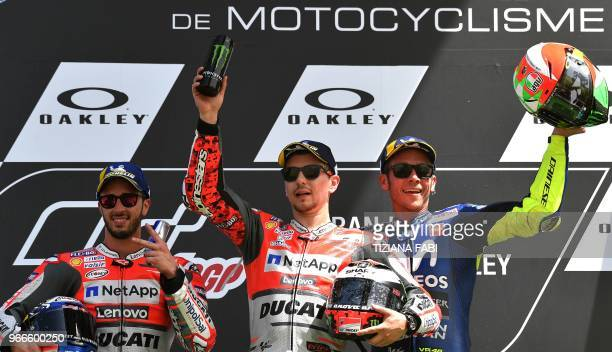Ducati Team's Spanish rider Jorge Lorenzo poses on the podium with second placed Ducati's Team rider Italian Andrea Dovizioso and third placed...