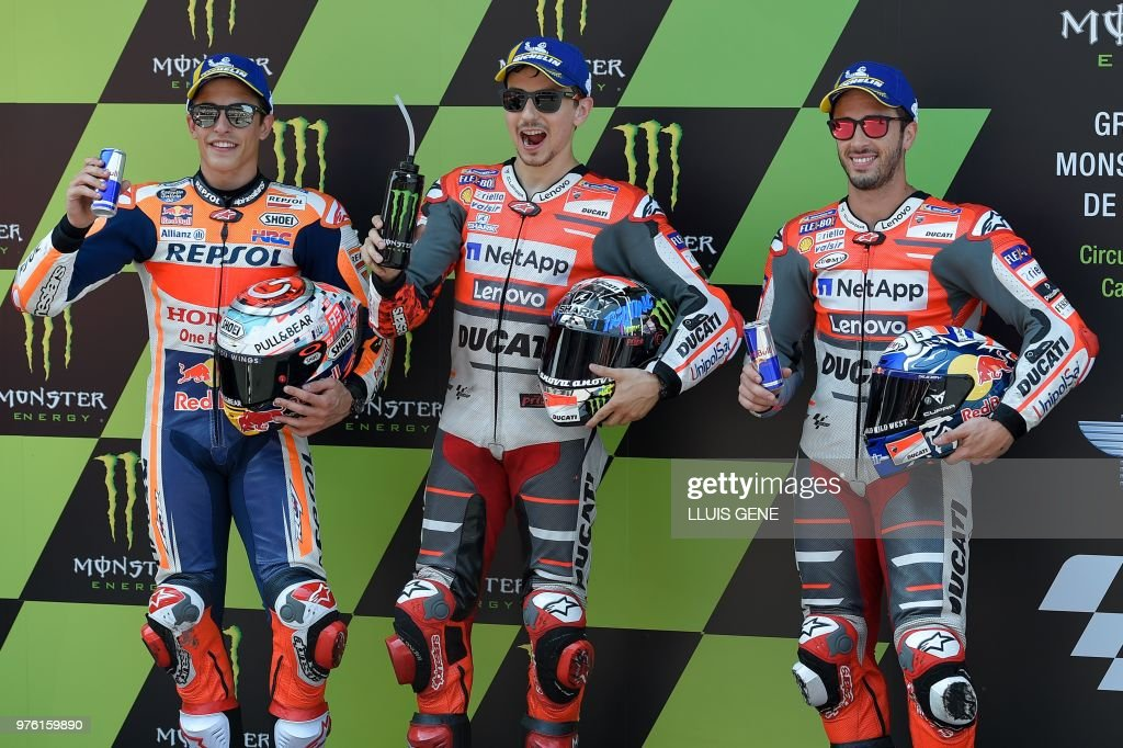 Ducati Team's Spanish rider Jorge Lorenzo (C), Repsol Honda's Spanish rider Marc Marquez (L) and Ducati Team's Italian rider Andrea Dovizioso (R) pose after the Catalunya MotoGP Grand Prix qualifying session at the Catalunya racetrack in Montmelo, near Barcelona on June 16, 2018.