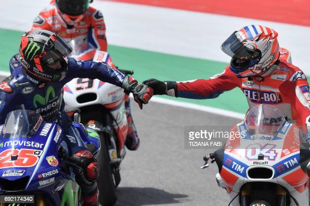 Ducati's Andrea Dovizioso celebrates with Movistar Yamaha's Spanish rider Maverick Vinales second after winning the Moto GP Grand Prix at the Mugello...