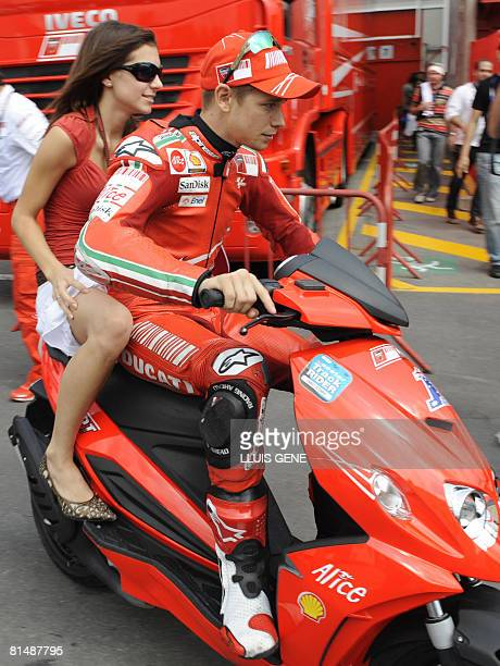 Ducati?s Australian Moto GP driver Casey Stoner rides a scooter with his wife after clinching pole position on June 7, 2008 at the Moto Grandprix of...