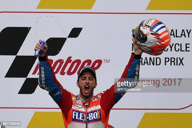 Ducati's Italian rider Andrea Dovizioso celebrates his victory on the podium after winning the Malaysia MotoGP at the Sepang International Circuit in...