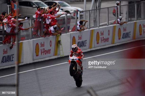 Ducati's Italian rider Andrea Dovizioso does a wheelie after winning the Malaysia MotoGP at the Sepang International circuit in Sepang on October 29,...