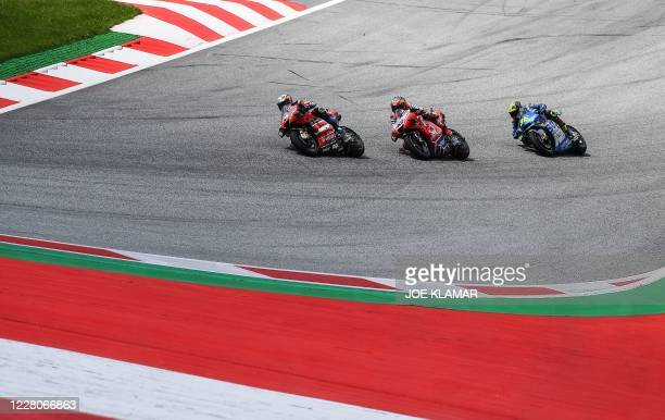 Ducati's Italian rider Andrea Dovizioso, Pramac Racing's Australian rider Jack Miller and Suzuki Ecstar's Spanish rider Joan Mir compete during the...
