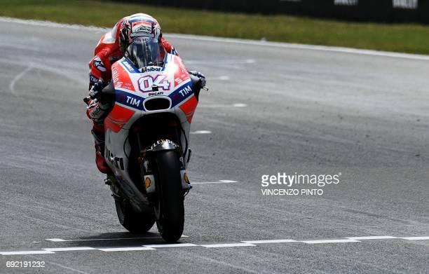 TOPSHOT Ducati's rider Italian Andrea Dovizioso crosses the finish line to win the Moto GP Grand Prix at the Mugello race track on June 4 2017...