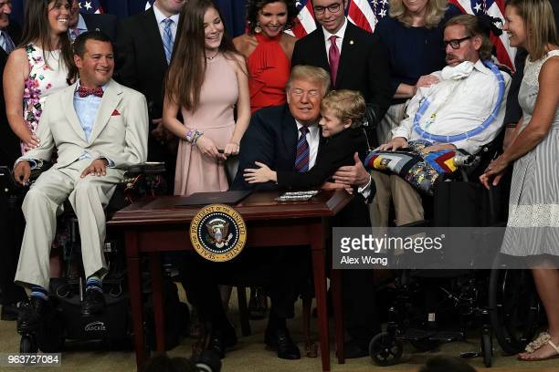 Duchenne Muscular Dystrophy patient Jordan McLinn of Indiana gives US President Donald Trump a hug during a bill signing ceremony at the South Court...
