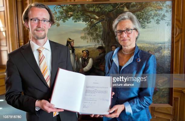 Duchess Donata Herzogin zu Mecklenburgvon Solodkoff and MecklenburgWestern Pomerania Culture Minister Mathias Brodkorb hold up the purchase agreement...