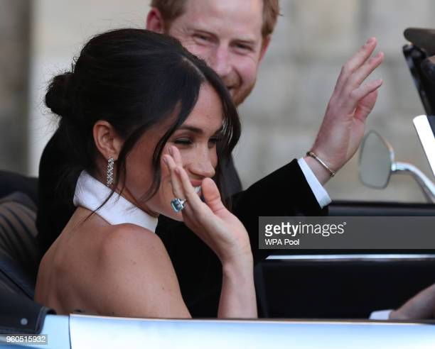 Duchess of Sussex and Prince Harry Duke of Sussex wave as they leave Windsor Castle after their wedding to attend an evening reception at Frogmore...