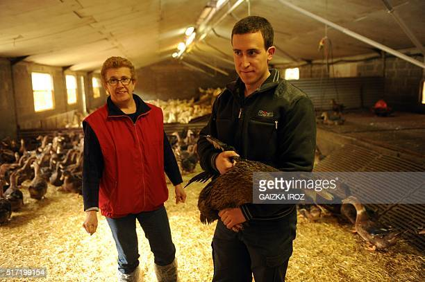 Duck breeders Florence and son Marc stand with ducks of the 'Criarde' breed in the stable of their farm in Bidache, southwestern France, on March 11,...