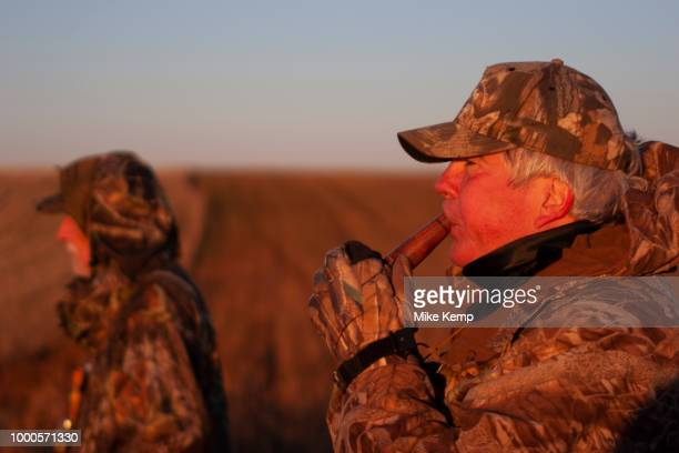 Duck hunting at dawn hunkered down for camouflage on a hilltop southeast of Minot North Dakota United States The duck hunters travel in the dark to...