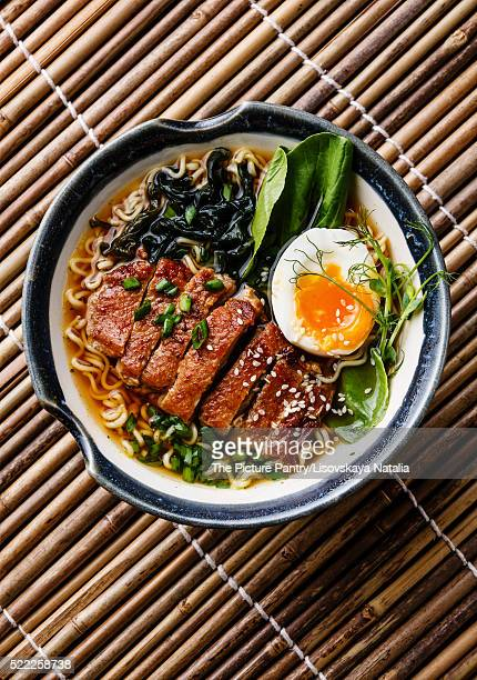 Duck noodles with egg and pak choi cabbage in bowl on bamboo background