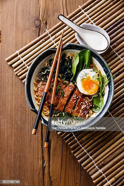 Duck noodles with egg and pak choi cabbage in bowl on wooden background