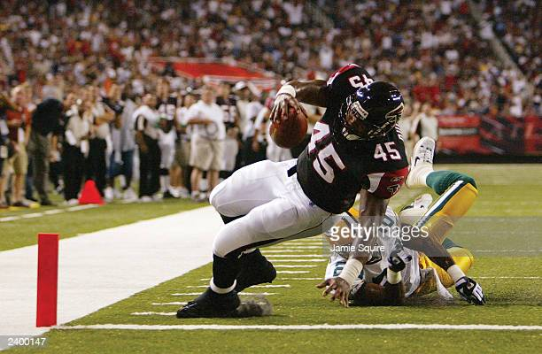 Duckett of the Atlanta Falcons crosses the goal line after catching a seven yard pass as Antuan Edwards of the Green Bay Packers misses the tackle in...