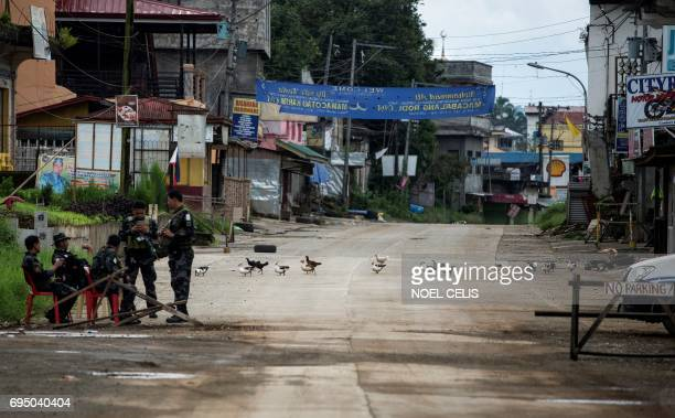 Ducks and chickens cross a street near a police checkpoint in Marawi on the southern island of Mindanao on June 12 2017 Embattled Philippine troops...