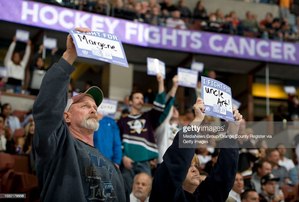 fd1f8a142ad Ducks  fans hold up signs during Hockey Fights Cancer Awareness ...
