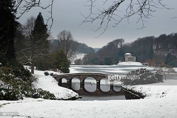 Ducks swim under a bridge crossing the frozen lake at the National Trust's Stourhead near Warminster on January 12 2010 in Wiltshire England Much of...