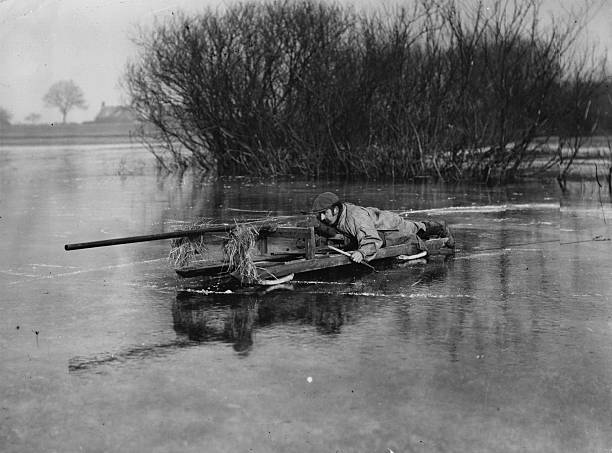 A duckshooter stalking birds on a sledge with a punt...