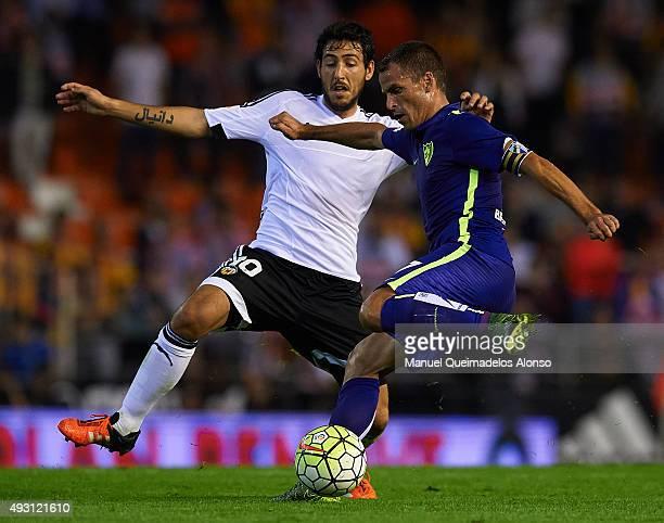 Duda of Malaga is tackled by Daniel Parejo of Valencia during the La Liga match between Valencia CF and Malaga CF at Estadi de Mestalla on October 17...