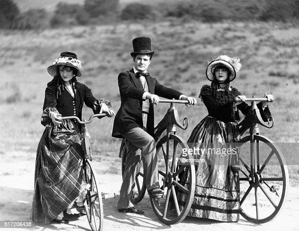 Dude with two belles about to embark on walking machine outing from the silent film Not So Long Ago