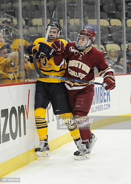 Dudek of the Boston College Eagles checks Brogan Rafferty of the Quinnipiac Bobcats into the boards in the second period during game one of the Three...