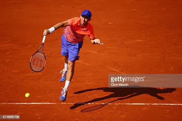 Dudi Sela of Israel serves in his Men's Singles match against JoWilfried Tsonga of France during day four of the 2015 French Open at Roland Garros on...