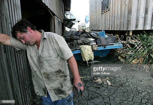 Dudley Major rests his head on his arm while taking a break from cleaning his father's home in the heavily damaged Venetian Isles neighborhood...