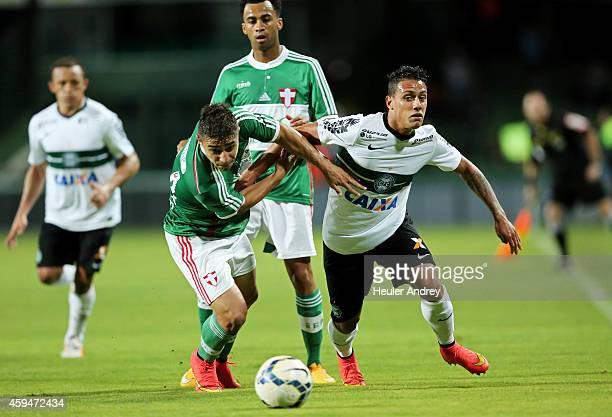 Dudu of Coritiba competes for the ball with Joao Pedro of Palmeiras during the match between Coritiba and Palmeiras for the Brazilian Series A 2014...