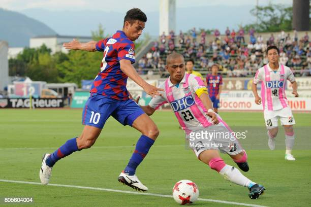 Dudu of Ventforet Kofu and Yutaka Yoshida of Sagan Tosu compete for the ball during the JLeague J1 match between Ventforet Kofu and Sagan Tosu at...