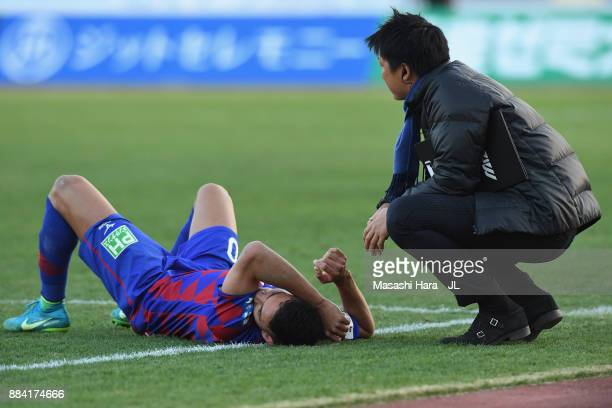 Dudu of Ventforet Kofu is consoled by a team staff after the relegation to the J2 despite his side's 10 victory in the JLeague J1 match between...