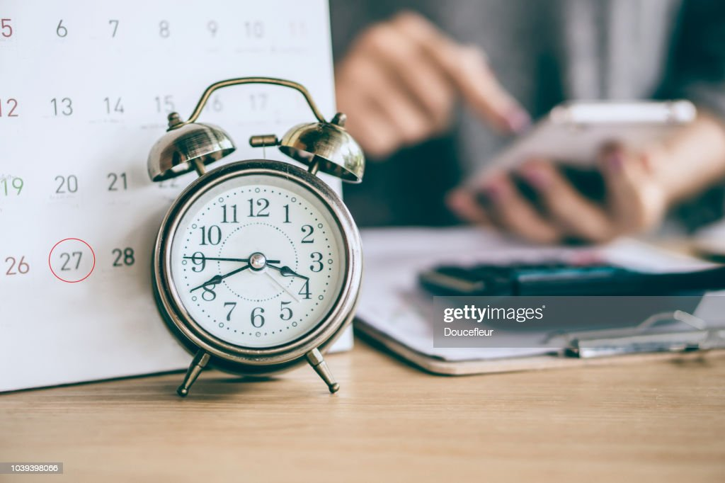 due date calendar and alarm clock with blur business woman hand calculating : Stock Photo