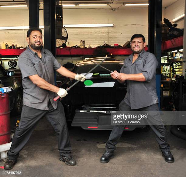 dueling auto mechanics having fun - yonkers stock pictures, royalty-free photos & images