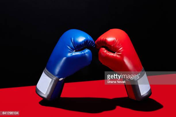 dueling boxing gloves - boxing gloves stock photos and pictures
