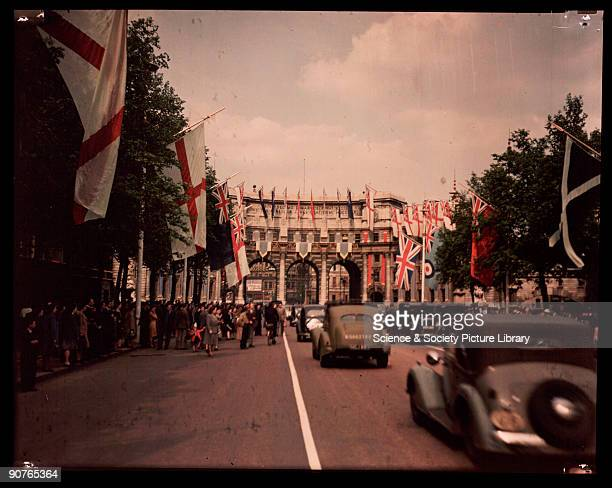 Dufaycolor colour transparency of Admiralty Arch, London, taken by an unknown photographer in May 1945. The Mall is lined with the flags of the...