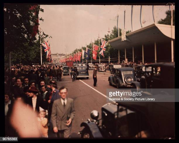 Dufaycolor colour transparency of crowds on The Mall in London, taken by an unknown photographer in May 1945. Traffic heads down the Mall towards...