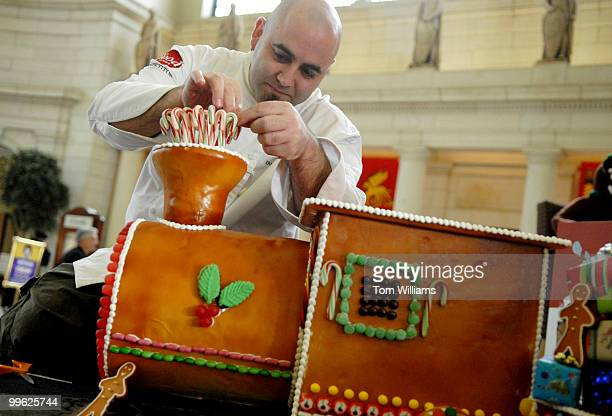 Duff Goldman host of Food Network's Ace of Cakes creates a gingerbread cake in the form of a train to accompany a lifesize Starbucks Gingerbread...