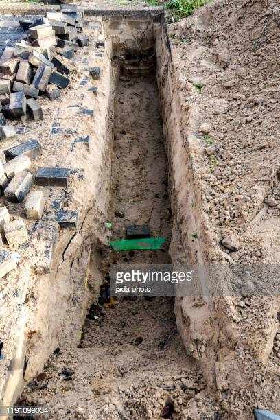 dug pit for construction work surrounded by paving stones - trench stock pictures, royalty-free photos & images