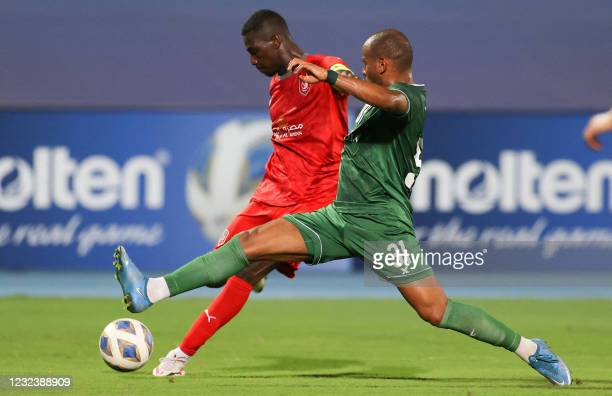 Duhail's forward Almoez Ali attempts a shot as he is marked by Ahli's defender Hani al-Sebyani during the AFC Champions League group C match between...