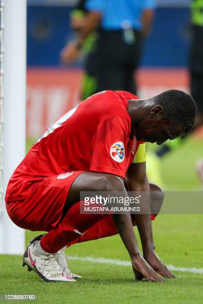 Duhail's forward Almoez Ali waits for treatment for a head wound during the AFC Champions League group C match between Qatar's AlDuhail and Saudi's...