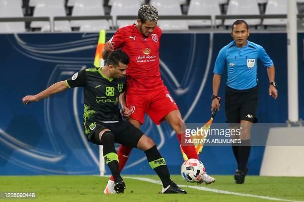 Duhail's forward Edmilson Silva is marked by Taawoun's midfielder Hamdan AlRuwaili during the AFC Champions League group C match between Qatar's...