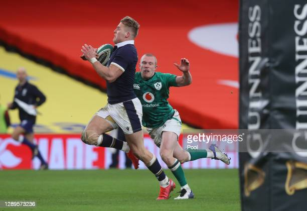 Duhan van der Merwe of Scotland runs in to score their first try chased by Keith Earls of Ireland during the Autumn Nations Cup match between Ireland...