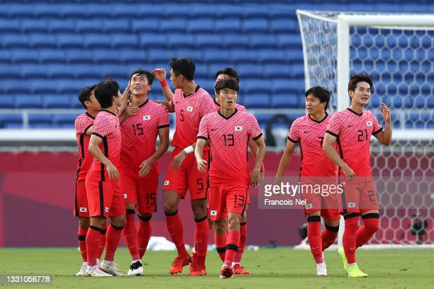 Dujae Won of Team South Korea celebrates with teammates after scoring their side's second goal from the penalty spot during the Men's Group B match...