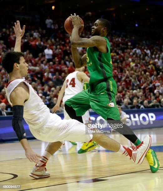 Duje Dukan of the Wisconsin Badgers draws a foul against Elgin Cook of the Oregon Ducks during the third round of the 2014 NCAA Men's Basketball...