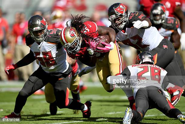 DuJuan Harris of the San Francisco 49ers carries the ball and gets tackled by Vernon Hargreaves and William Gholston of the Tampa Bay Buccaneers...