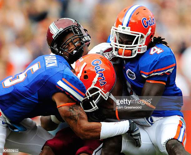 DuJuan Harris of the Troy Trojans is tackled by Wondy PierreLouis and Joe Haden of the Florida Gators during the game at Ben Hill Griffin Stadium on...
