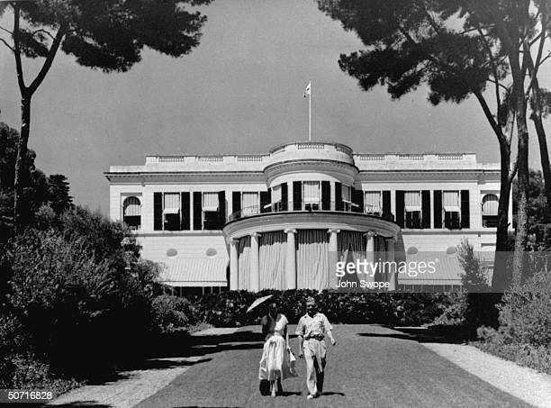 Duke and Duchess of Windsor walking in front of mansion
